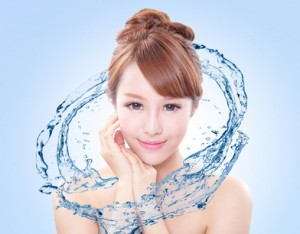Beautiful portrait of woman with fresh skin in splashes of water , concept for beauty skin care isolated on blue background, asian model